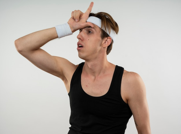 Jeune homme sportif regardant côté portant un bandeau et un bracelet montrant le geste de perdant isolé sur un mur blanc