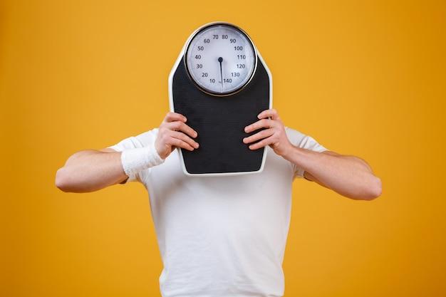Jeune homme sportif se cachant le visage derrière des échelles de poids