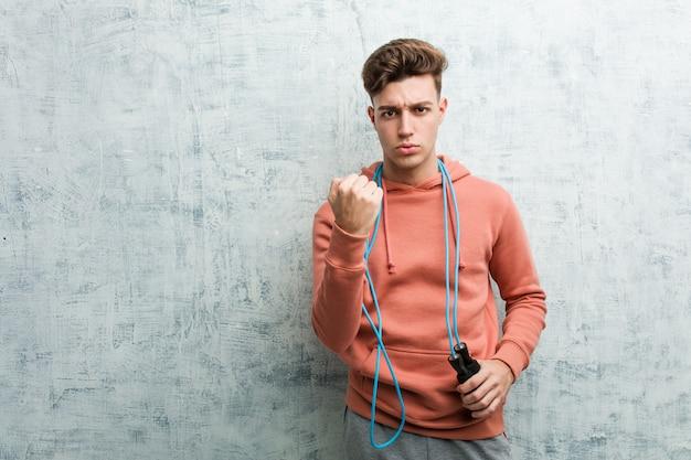 Jeune homme sportif tenant une corde à sauter montrant le poing à la caméra, expression faciale agressive.