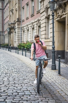 Jeune homme sportif à vélo dans une ville européenne. sports en milieu urbain.