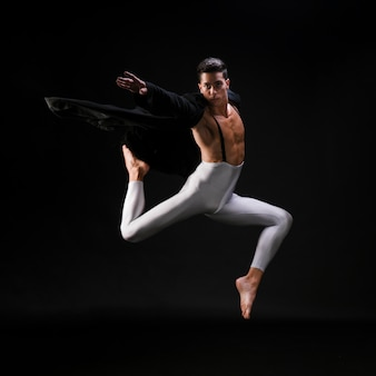 Jeune homme sportif en vêtements élégants, sautant et dansant