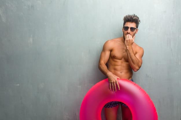 Jeune homme sportif, vêtu d'un maillot de bain contre un mur de grunge se ronger les ongles