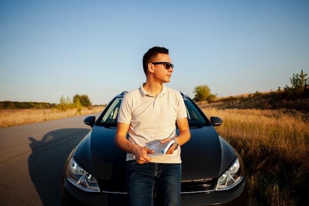 Jeune homme, stationnement, bord route