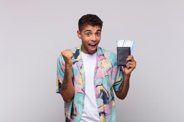 Jeune homme sud-américain se sentant choqué, excité et heureux, riant et célébrant le succès, disant wow!