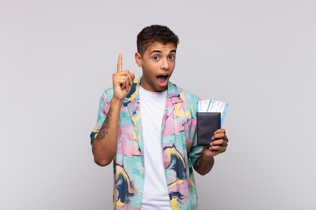 Jeune homme sud-américain se sentant comme un génie heureux et excité après avoir réalisé une idée, levant joyeusement le doigt, eureka!