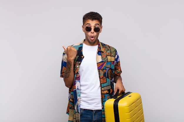 Jeune homme sud-américain à la stupéfaction, pointant sur l'objet sur le côté et disant wow, incroyable