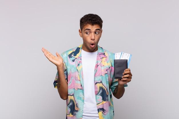 Jeune homme sud-américain à la surprise et choqué, avec la mâchoire tombée tenant un objet avec une main ouverte sur le côté