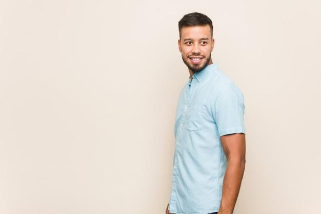 Jeune homme sud-asiatique regarde de côté souriant, joyeux et agréable.