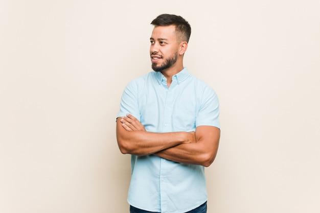 Jeune homme sud-asiatique souriant confiant avec les bras croisés.