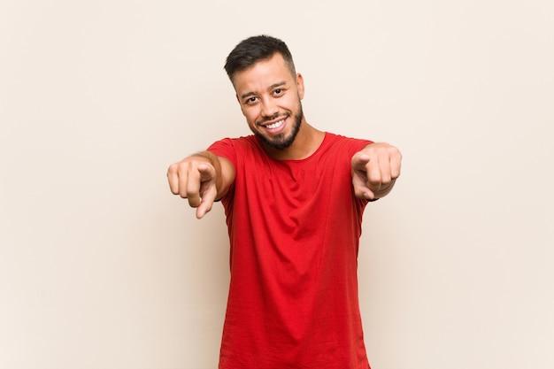 Jeune homme sud-asiatique sourires joyeux pointant vers l'avant.