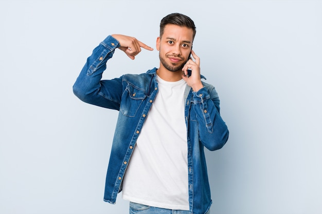Jeune homme sud-asiatique tenant un téléphone