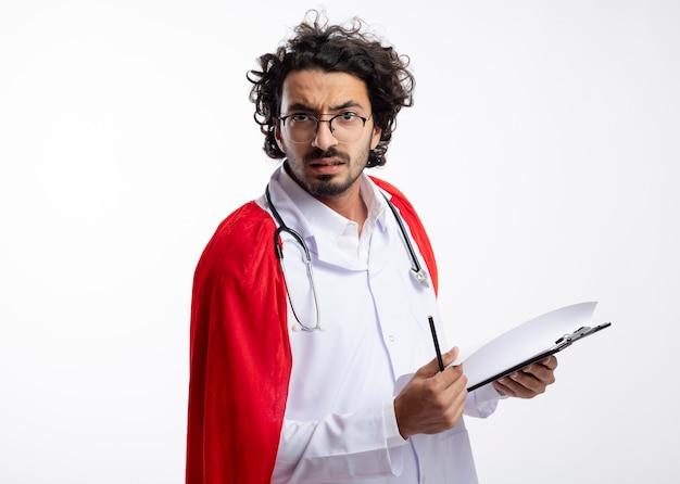 Un jeune homme de super-héros caucasien sérieux dans des lunettes optiques portant un uniforme de médecin avec une cape rouge et un stéthoscope autour du cou tient un crayon et un presse-papiers