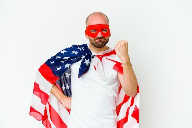 Jeune homme de super-héros isolé sur un mur blanc montrant le poing à la caméra, expression faciale agressive.