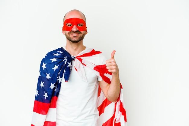 Jeune homme de super-héros isolé sur un mur blanc souriant et levant le pouce vers le haut