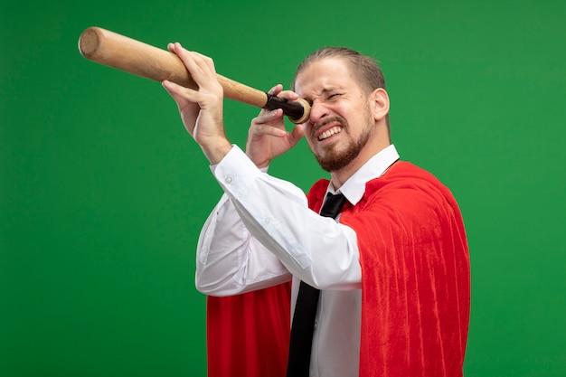 Jeune homme de super-héros montrant le geste de regard avec une batte de baseball isolé sur vert