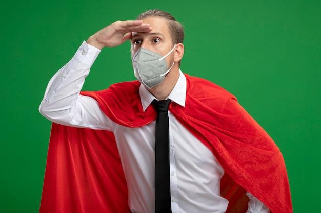 Jeune homme de super-héros portant un masque médical et une cravate à la recherche à distance avec la main isolé sur vert