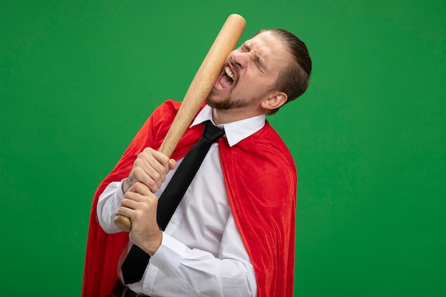 Jeune homme de super-héros se battre avec une batte de baseball isolé sur vert