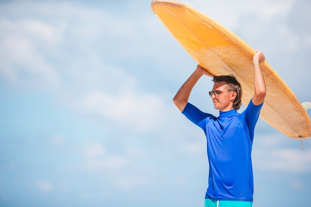 Jeune homme de surf à la plage blanche avec planche de surf jaune