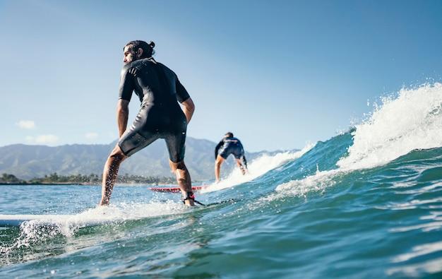 Jeune homme surfe sur les vagues de l'océan