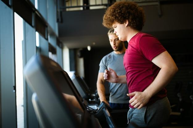 Jeune homme en surpoids avec entraîneur exerçant dans une salle de sport. sport, santé, concept de surpoids