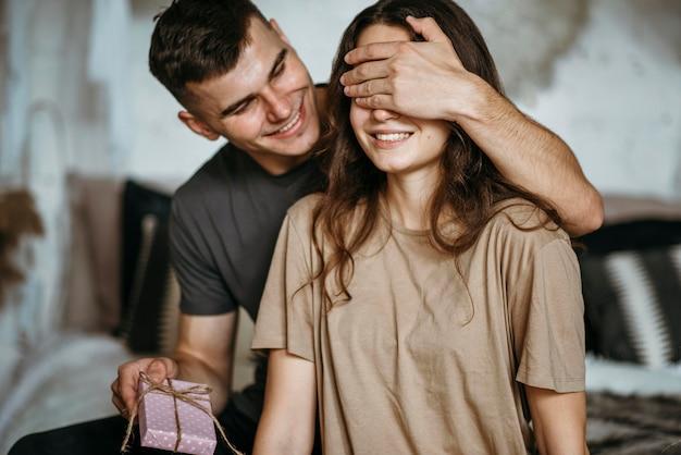 Jeune homme surprenante petite amie avec cadeau