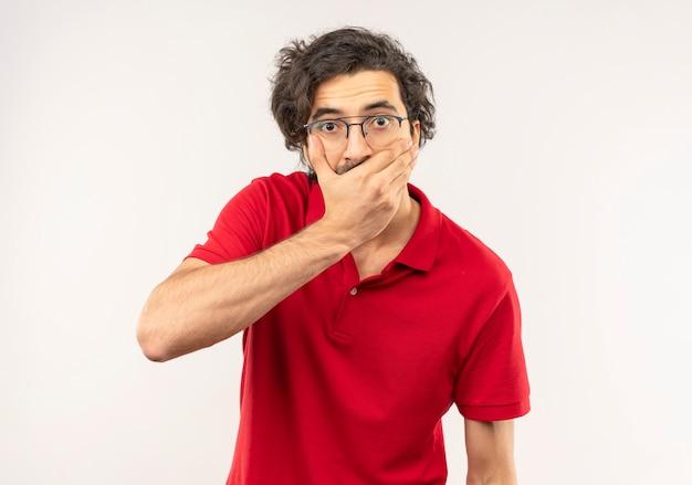 Jeune homme surpris en chemise rouge avec des lunettes optiques met la main sur la bouche et semble isolé sur un mur blanc