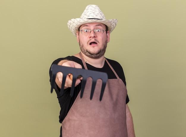 Jeune homme surpris jardinier portant un chapeau de jardinage tenant un râteau à la caméra isolé sur un mur vert olive