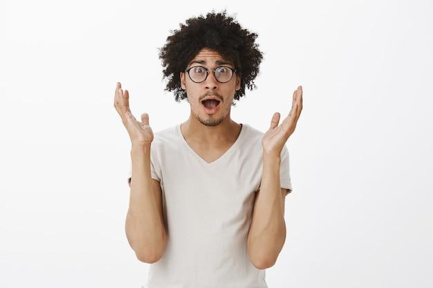 Un jeune homme surpris, plein d'espoir, levant les mains soulagé, reçoit de bonnes nouvelles