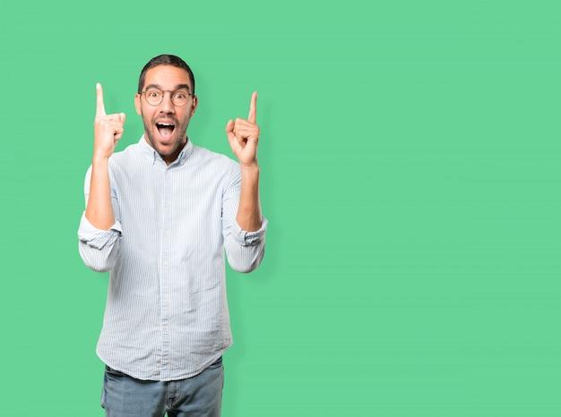 Jeune homme surpris pointant vers le haut avec son doigt