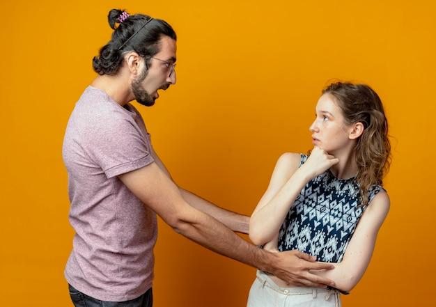 Jeune homme à la surprise de sa petite amie alors qu'elle le regarde perplexe sur le mur orange