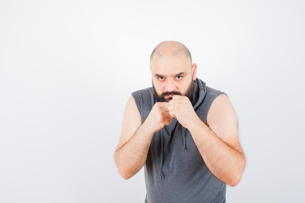 Jeune homme en sweat à capuche sans manches debout dans une pose de combat et l'air confiant, vue de face.