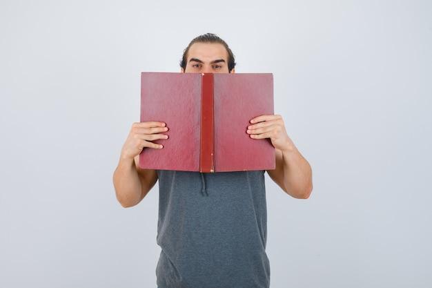 Jeune homme en sweat à capuche sans manches tenant un livre ouvert sur la bouche et à la grave, vue de face.