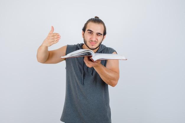Jeune homme en sweat à capuche sans manches tenant un livre ouvert tout en étirant la main dans un geste d'interrogation et à la curieuse, vue de face.