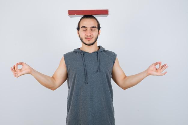 Jeune homme en sweat à capuche sans manches tenant un livre sur la tête tout en montrant le geste de méditation et à la vue de face, paisible.