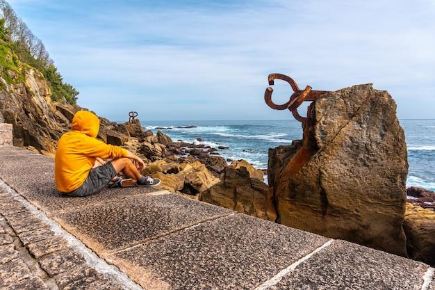 Un jeune homme en sweat jaune visitant la peine del viento à san sebastiã¡n