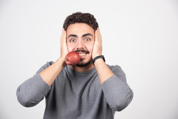Jeune homme en sweat-shirt gris tenant la pomme dans sa bouche.