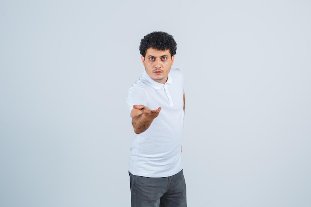 Jeune homme en t-shirt blanc et jeans étirant les mains vers la caméra et regardant sérieux, vue de face.