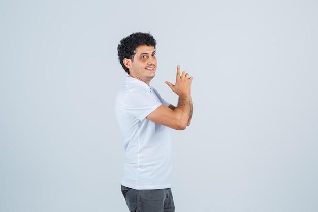 Jeune homme en t-shirt blanc et jeans montrant le geste du pistolet et l'air heureux, vue de face.