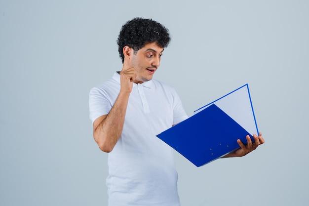 Jeune homme en t-shirt blanc et jeans tenant un dossier, le regardant et l'air concentré, vue de face.