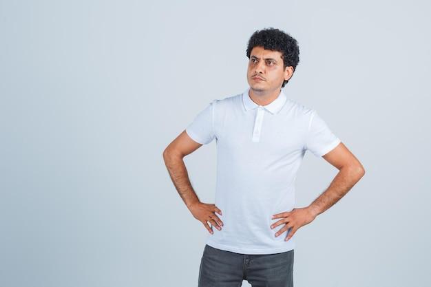 Jeune homme en t-shirt blanc et jeans tenant les mains sur la taille et l'air pensif, vue de face.