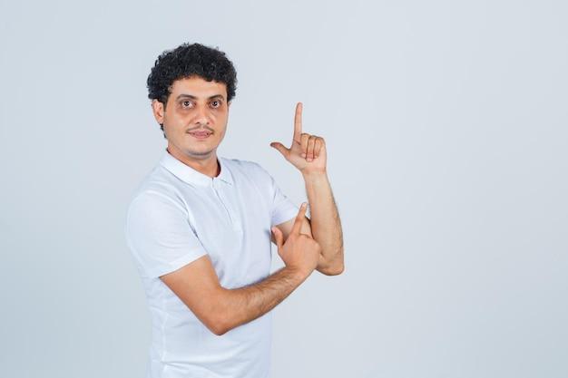 Jeune homme en t-shirt blanc montrant le geste du pistolet et l'air confiant, vue de face.
