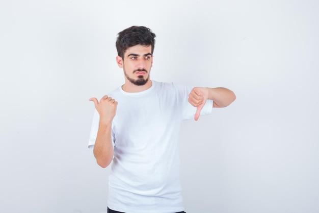 Jeune homme en t-shirt blanc montrant le pouce vers le bas, pointant vers l'extérieur et l'air confiant