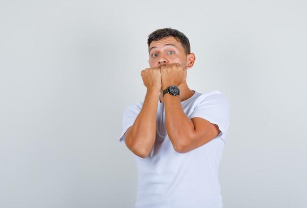 Jeune homme en t-shirt blanc mordre les poings et à la vue de face, nerveux.