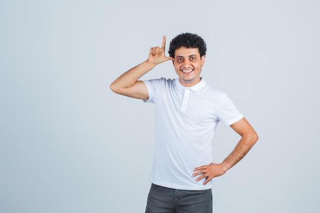 Jeune homme en t-shirt blanc, pantalon montrant le geste du pistolet et l'air heureux, vue de face.