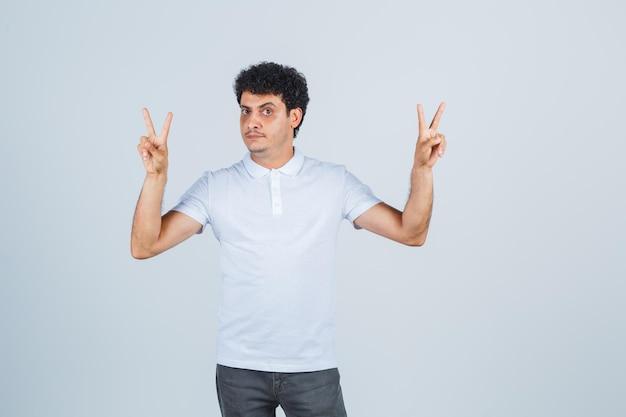 Jeune homme en t-shirt blanc, pantalon montrant le geste de la victoire et l'air confiant, vue de face.