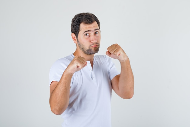 Jeune homme en t-shirt blanc se présentant comme un boxeur et à la forte