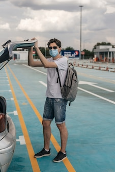 Jeune homme en t-shirt blanc, short en jean, lunettes de soleil et masque chirurgical avec sac à dos sur le dos. à travers la vue de la voiture