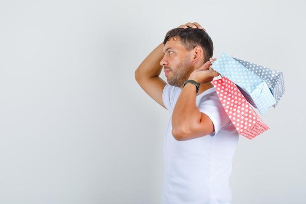 Jeune homme en t-shirt blanc tenant des sacs en papier avec la main sur la tête.