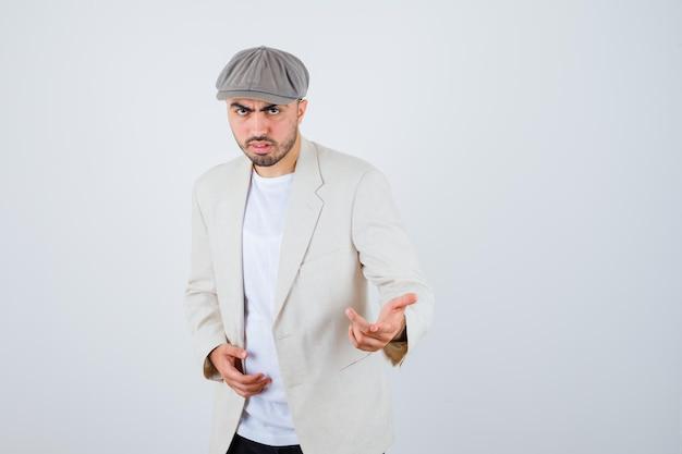 Jeune homme en t-shirt blanc, veste et casquette grise s'étendant les mains vers l'avant et ayant l'air sérieux