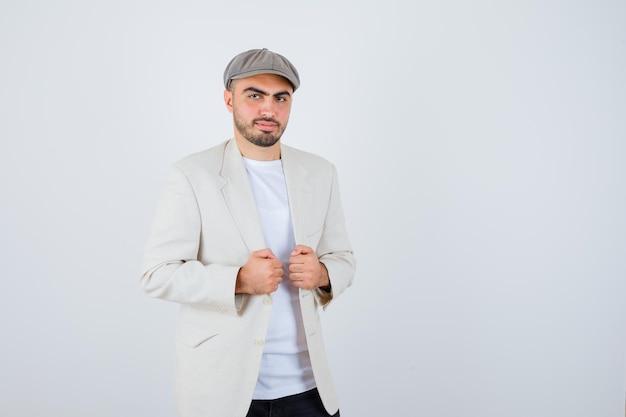 Jeune homme en t-shirt blanc, veste et casquette grise se tenant la main dans la veste et l'air sérieux